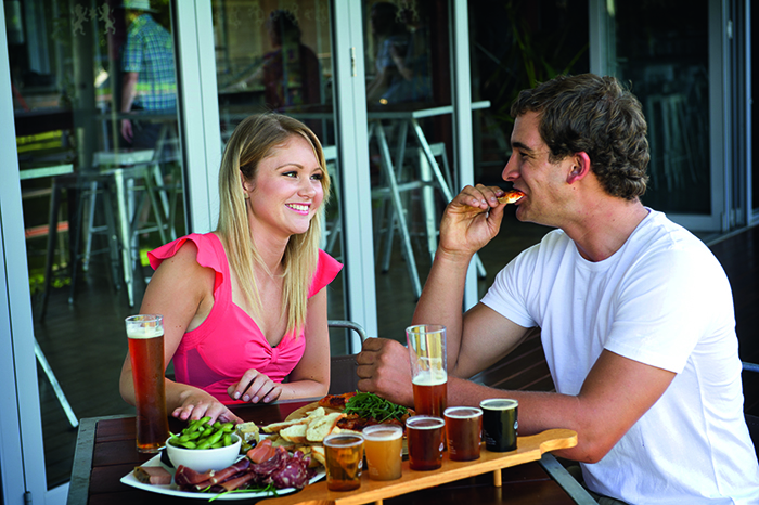 A man and woman at a brewery eating and drinking