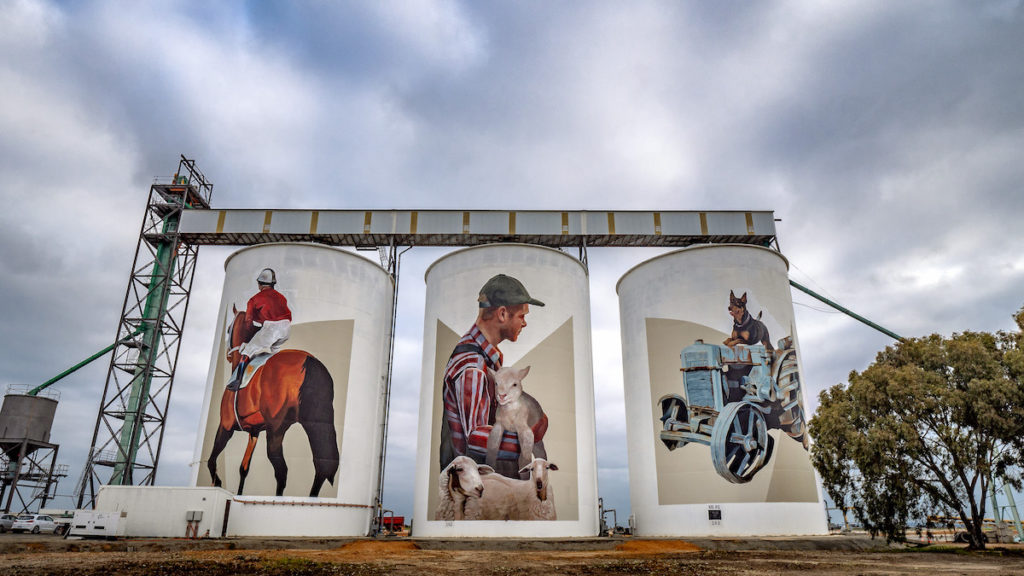 three art silos showing mural of man holding sheep, man on a horse and a dog on a blue tractor in Pingrup