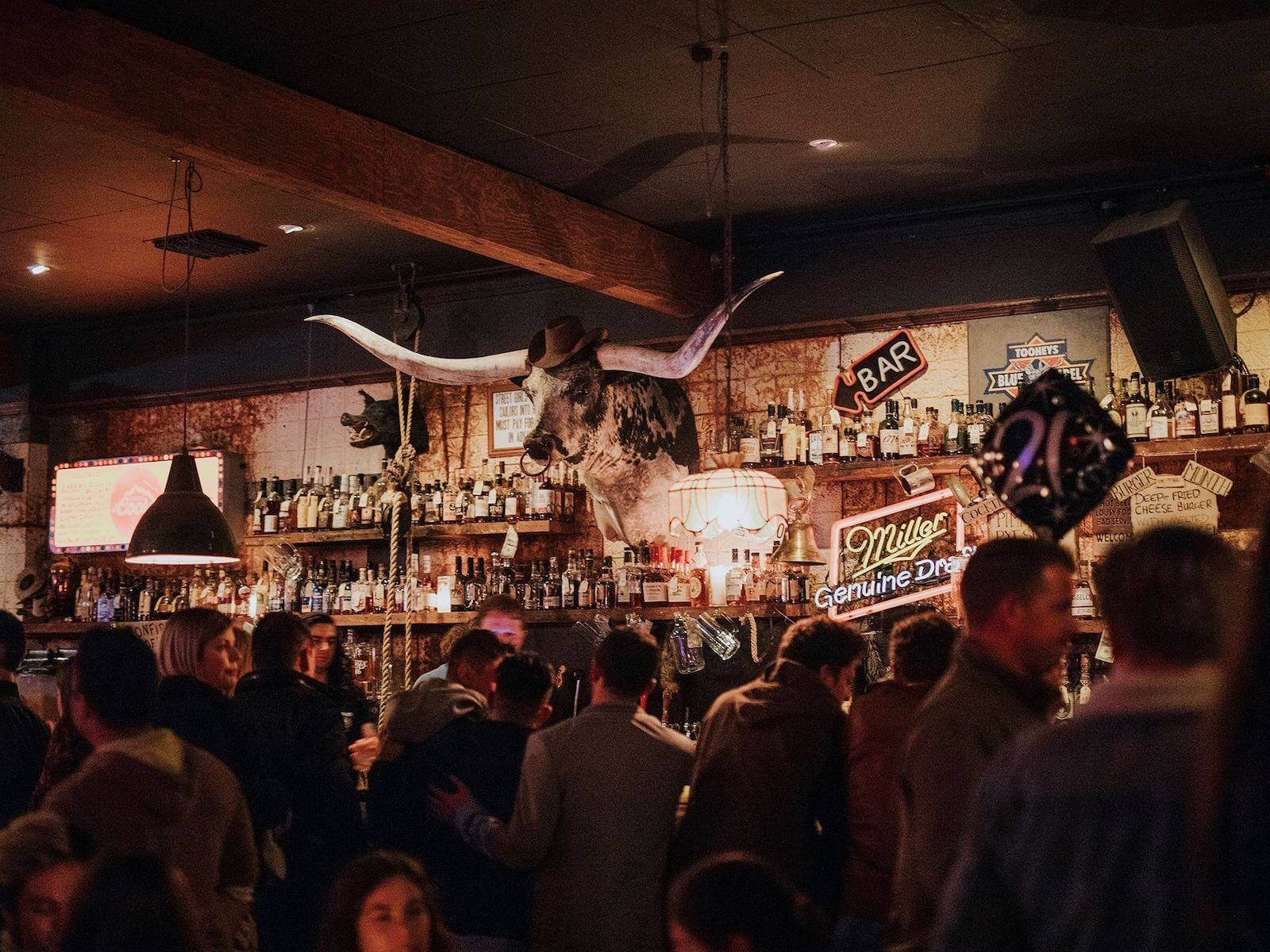 the bar at Alabama song packed out, showing the bull head and other American-style decor