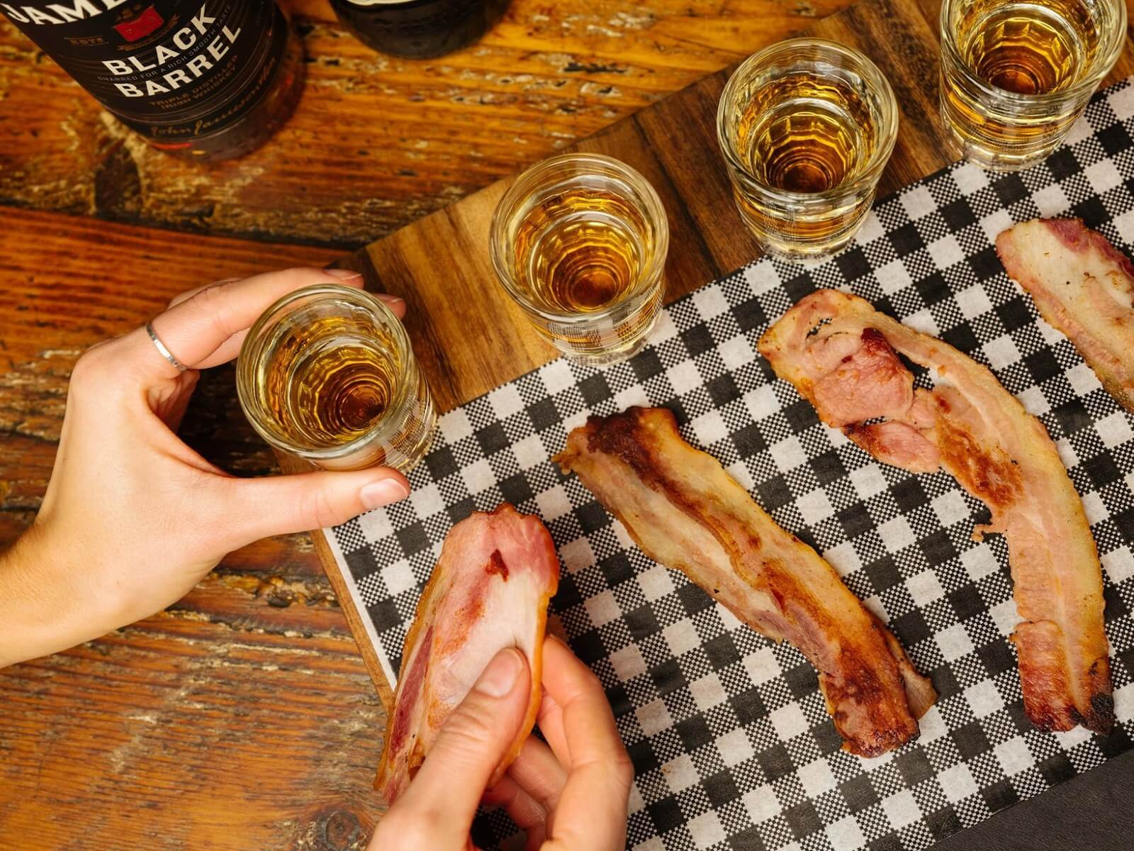 4 shots of whiskey on a table with a streak of bacon next to each to dip into the shot glass