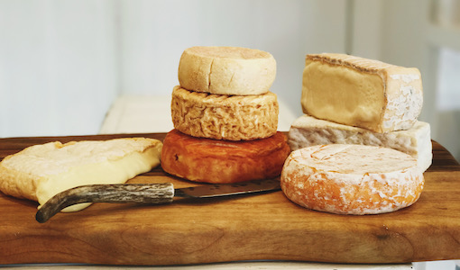 A large amount of unpackaged cheeses sit on a brown, wooden board, next to a cheese knife