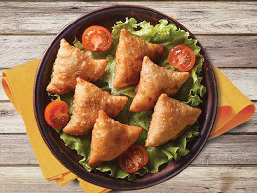 Six Triangle Samosas sit atop a salad