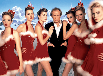 Bill Nigh stands with women in red Christmas dresses