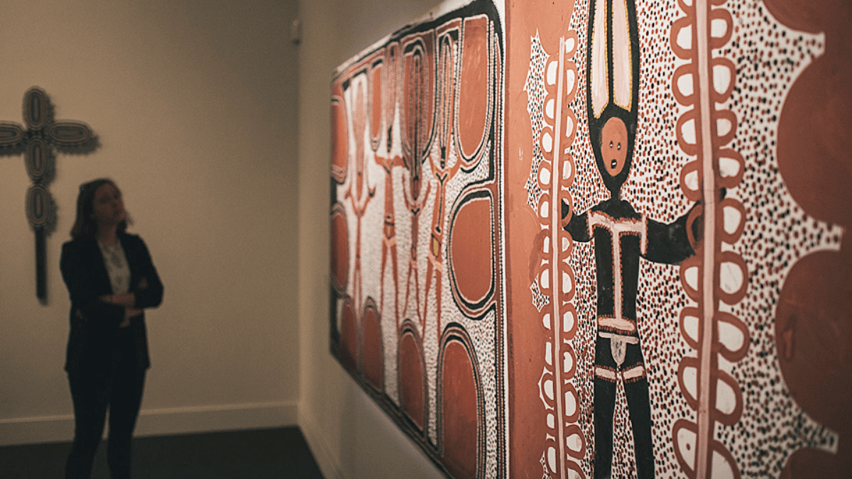 A woman observes a piece of indigenous art hanging on the wall