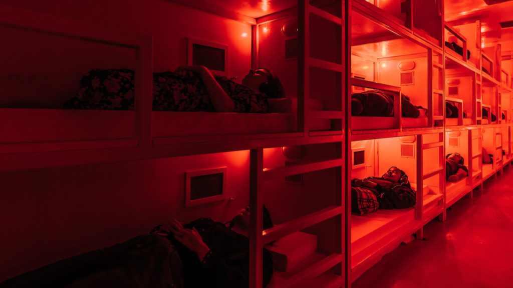 people laying in bunk beds in a red room with headphones in at COMA