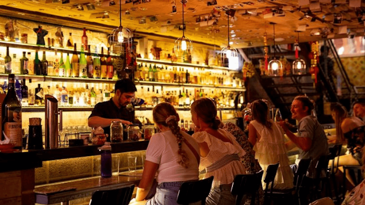 bar with people ordering from a bartender