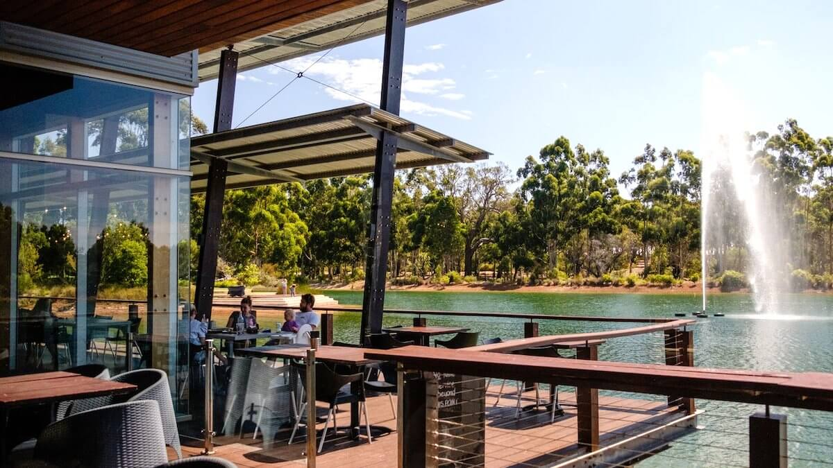People sit on an outdoor deck on a sunny day overlooking a lake with gum trees in the background