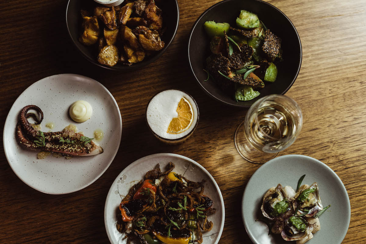 flat lay image of octopus, potatoes and several other food dishes and cocktails on a table at Clarences Company Store