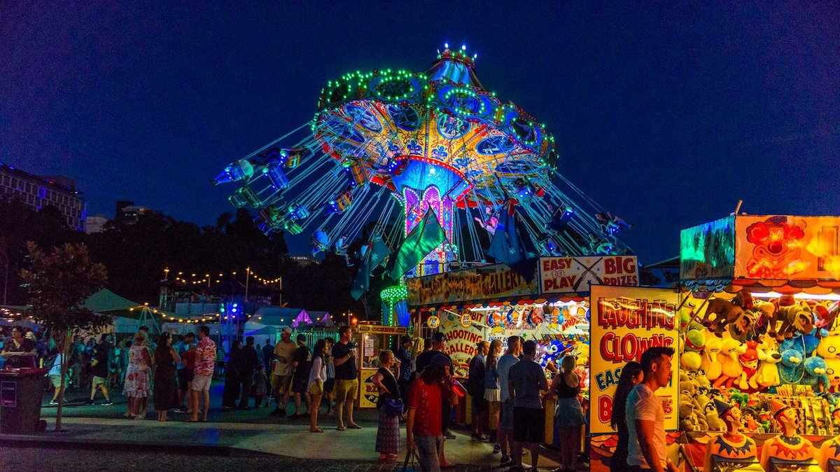 image showing a carnival ride and stalls at night at WA Cider and Pork Festival