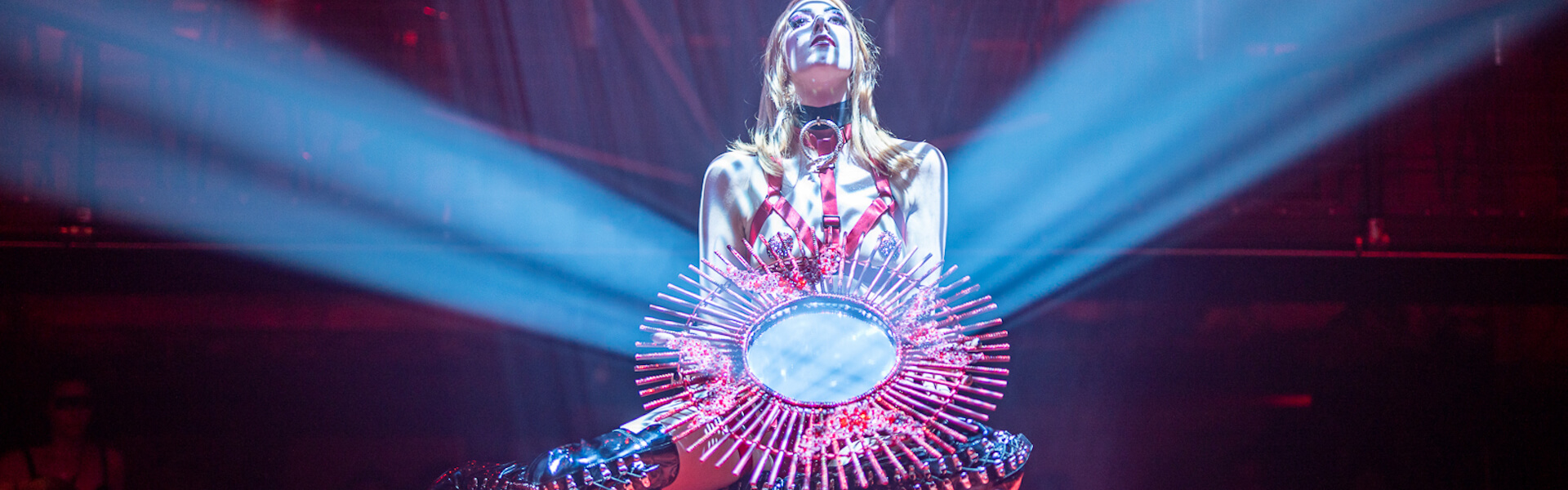 A woman in red harness lingerie holds a sun burst mirror and gazes into the spotlight