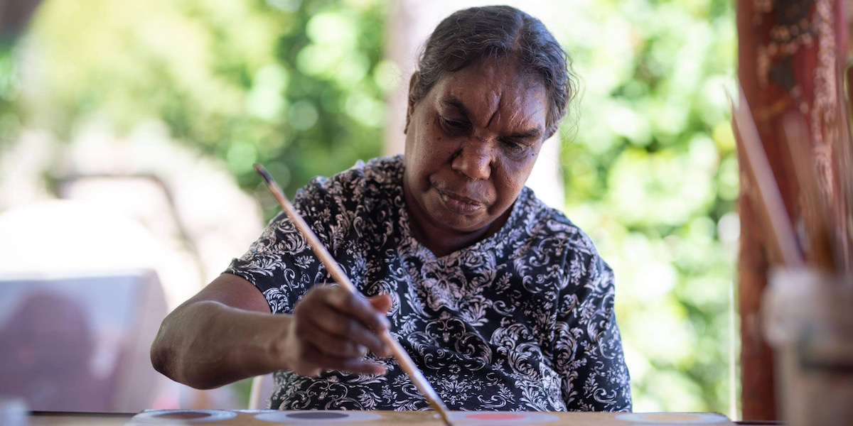 An older indigenous woman faces the camera, she is seated and holds a paintbrush in her left hand and is painting. The background is green and leafy. For Revealed Exhibition 2021
