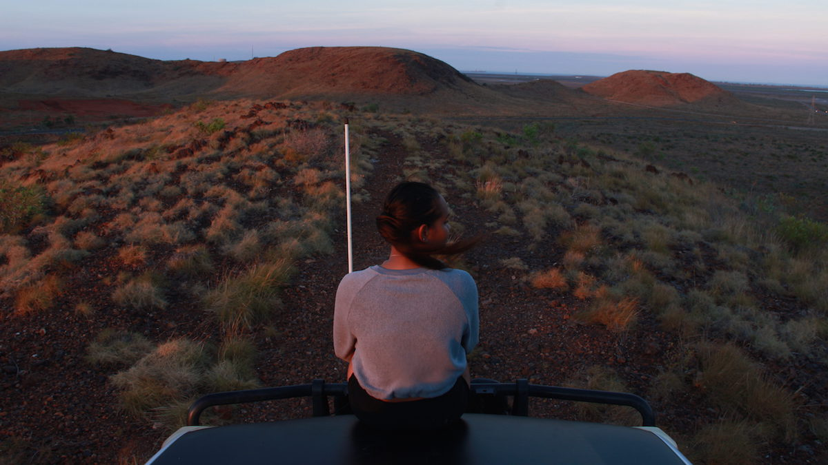 A girl looking into the distance sits on the hood of a 4WD at sunset, looking at the red dirt scrublands and small hills in the distance. She is looking to the right of the image. For Revealed Exhibition 2021