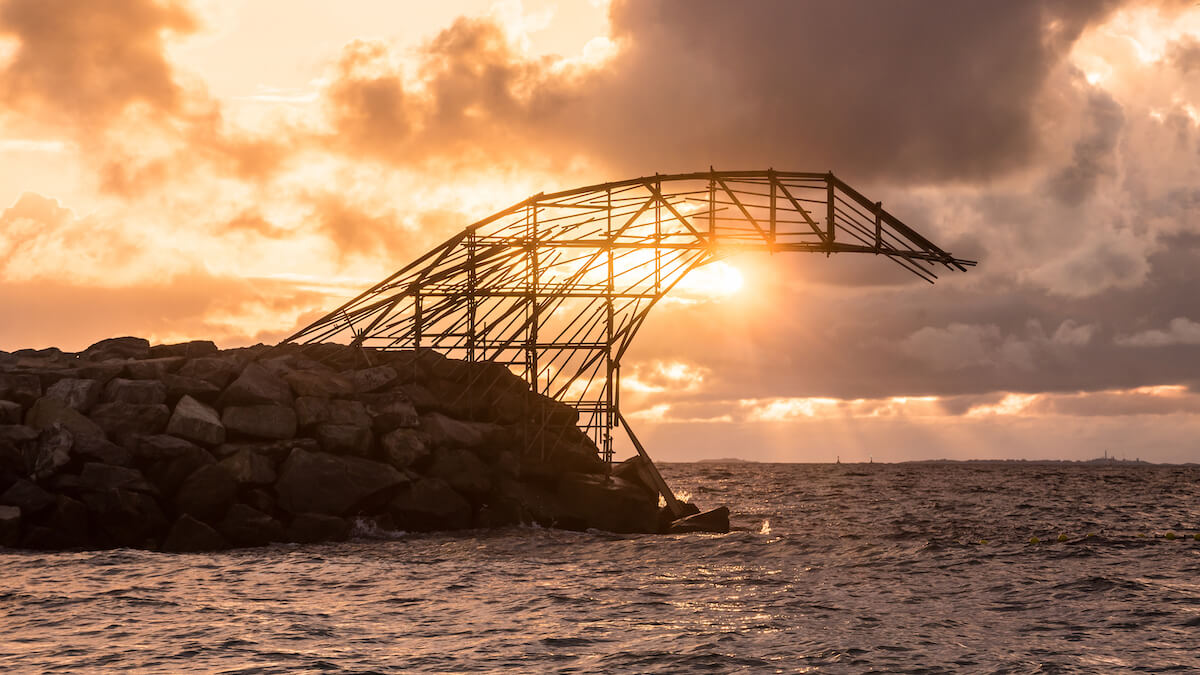 a wave made of scaffolding juts out from the stone groyne at Cottesloe Beach, it is sunset and the sun is seen shining just underneath the curve of the wave