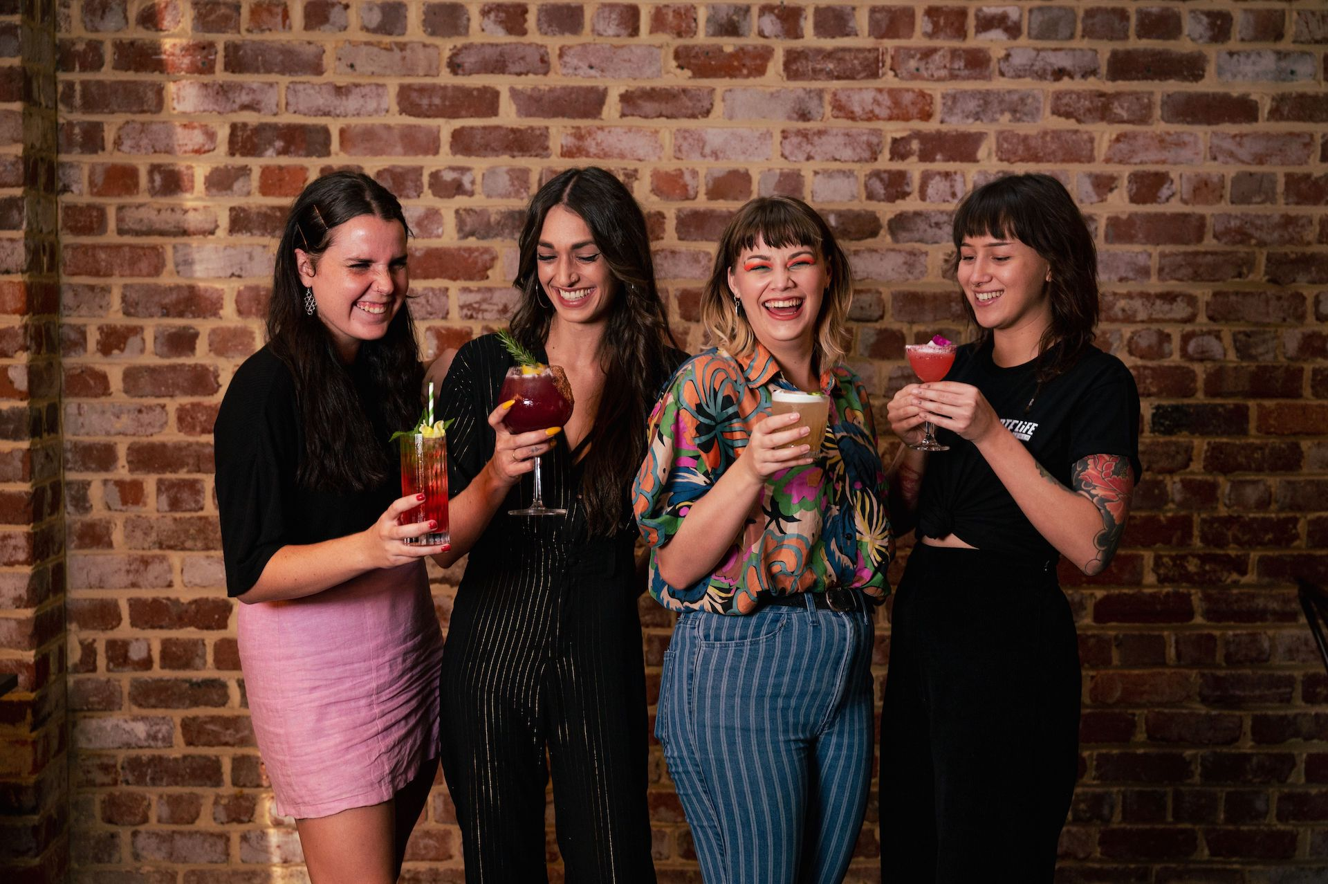 four women holding cocktails laughing