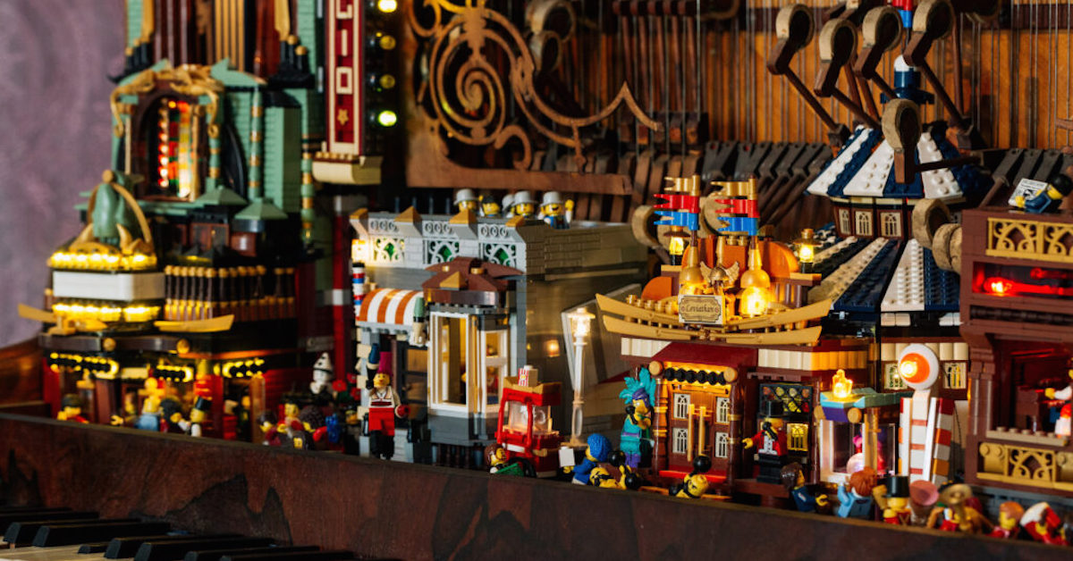 Complex LEGO buildings sit amongst the bowels of an old piano, complete with LEGO minifigure characters