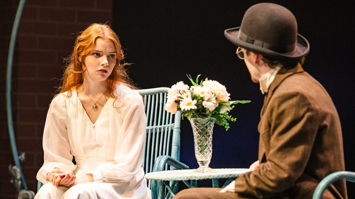 A woman with red hair and a white dress sits on a blue wicker chair in tense discussion with a man in a brown suit and a bowler hat. A vase of flowers sits on a small table between them