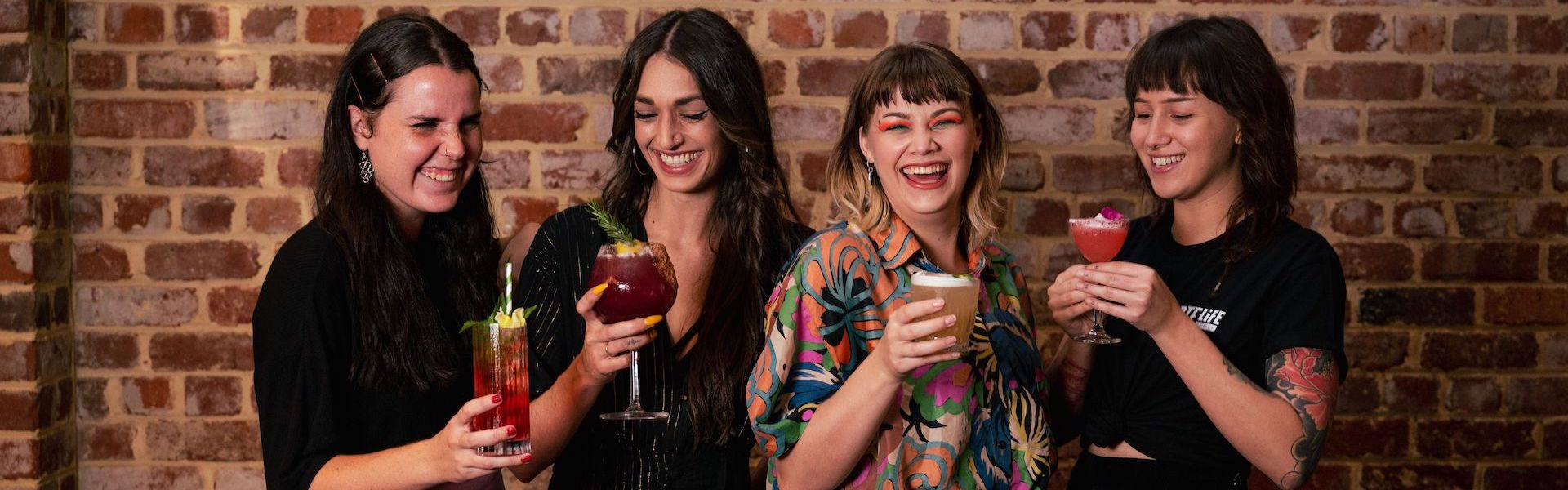 Four women hold cocktails and laugh