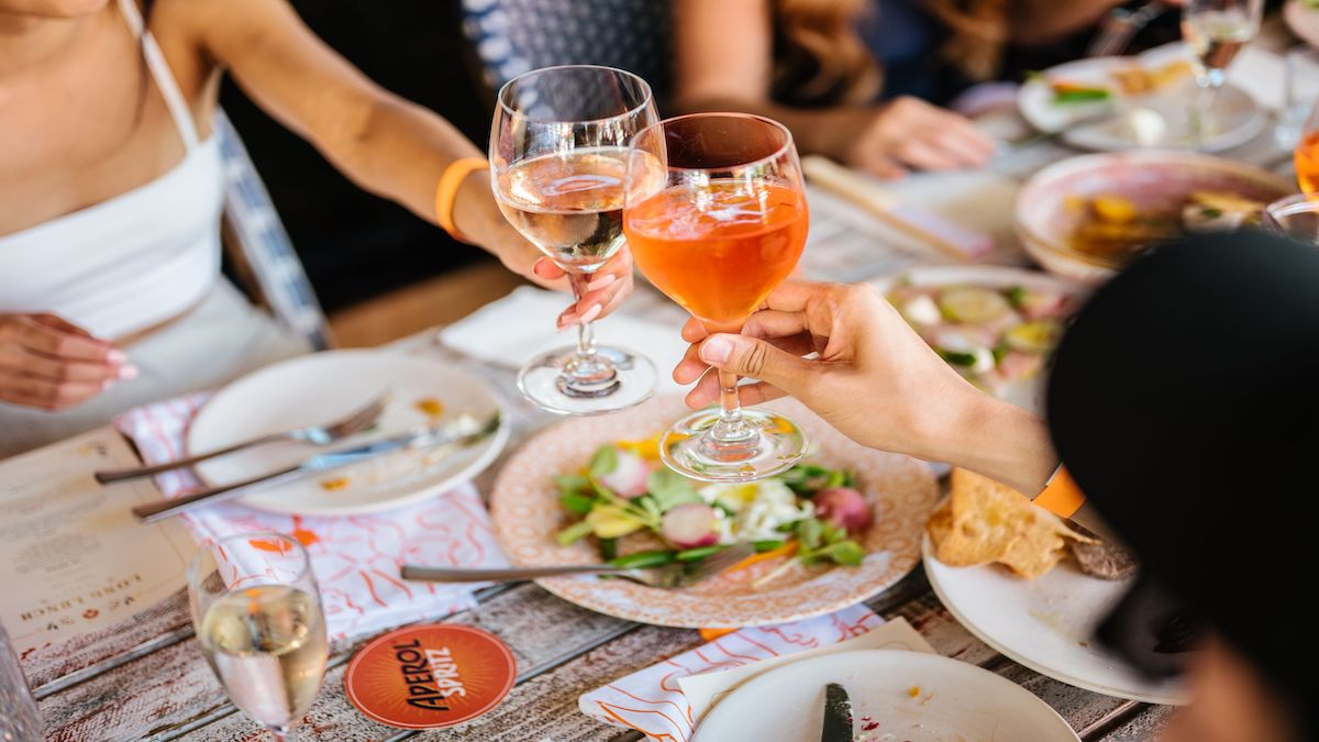 Two people clinking their wine glasses at a table filled with plates of food