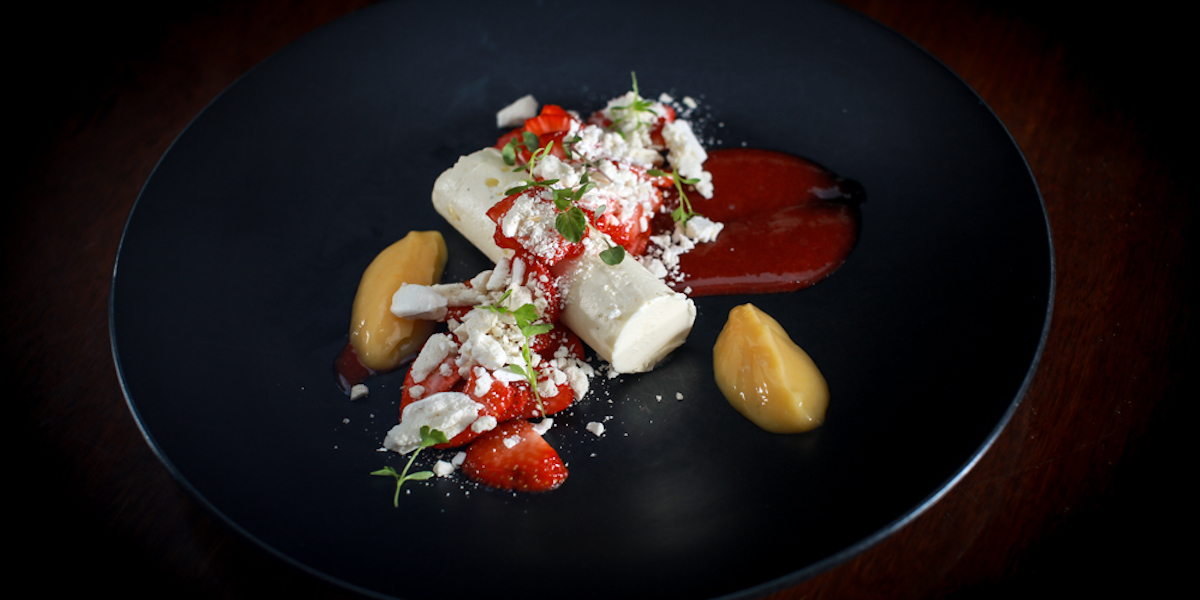 A delicately decorated dish from Sentinel that appears to have strawberries, mango puree and a sweet sauce.