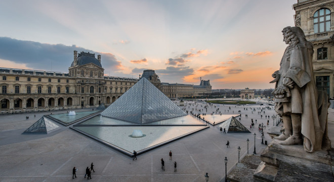 An image of the Louvre, with the glass pyramid centre of the image, just after sunset, with rays through the clouds still visible. There are distant people scattered around the square