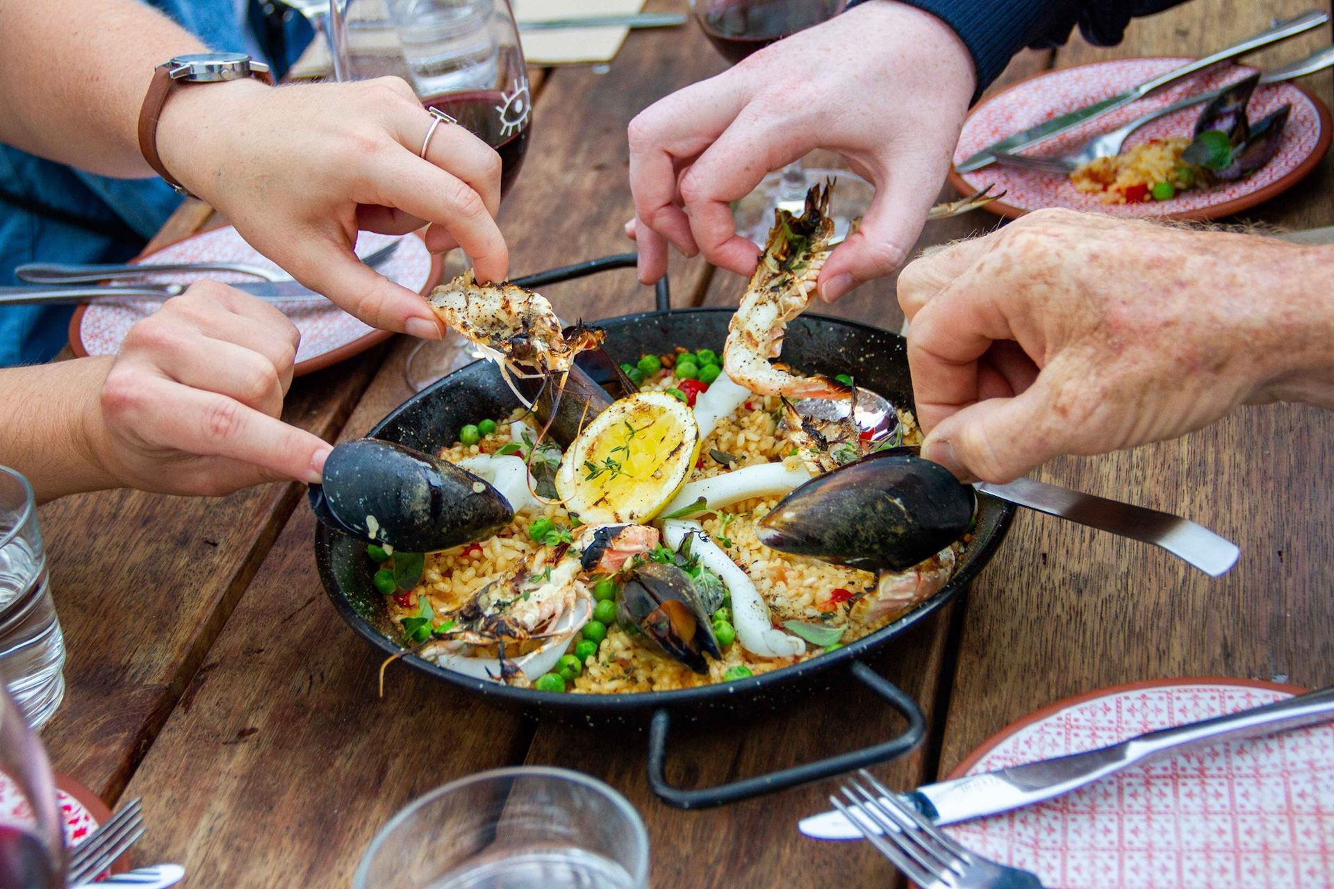 people digging into a paella