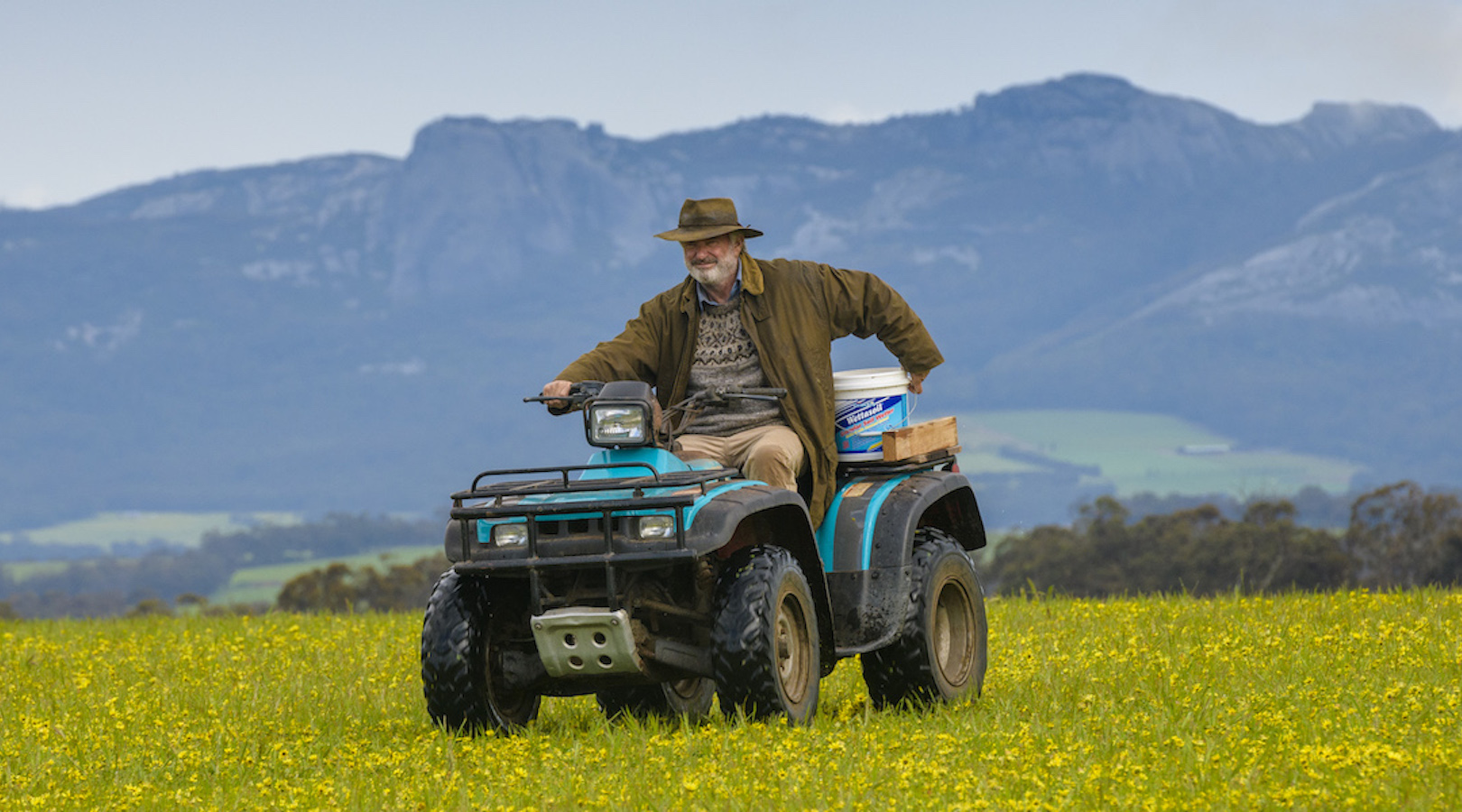 Sam Neill, atop a quad bike in typical faming gear and a broad brimmed hat, drives across a field of yellow wildflowers, with the Porongurup range in the background