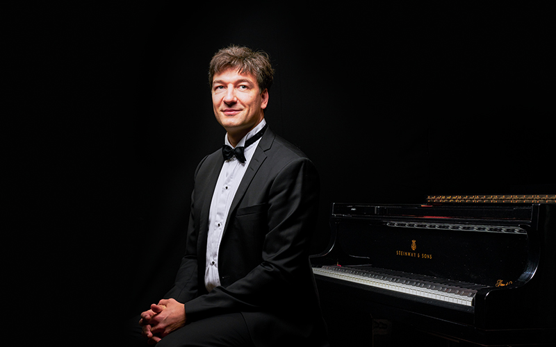 Pianist Konstantin Shamray sits on a piano stool looking into the distance, with a dark background