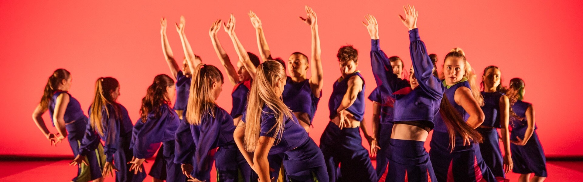 A group dressed in purple dance across an orange background